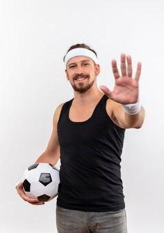 Sorridente giovane uomo sportivo bello che indossa la fascia e braccialetti in possesso di pallone da calcio e allungando la mano isolata su uno spazio bianco Foto Gratuite
