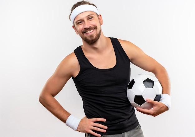 Sorridente giovane uomo sportivo bello indossando la fascia e braccialetti tenendo il pallone da calcio con la mano sulla vita isolato su uno spazio bianco