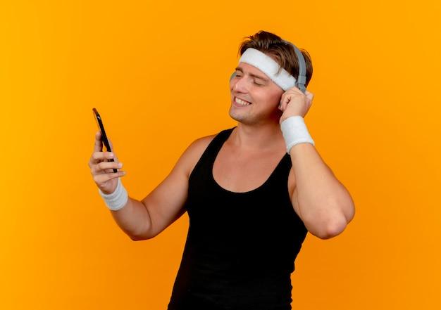 Sorridente giovane uomo sportivo bello indossando la fascia e braccialetti mettendo la mano sulle cuffie che tengono e guardando il telefono cellulare isolato sulla parete arancione