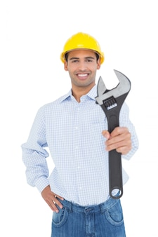 Smiling young handyman holding out a wrench
