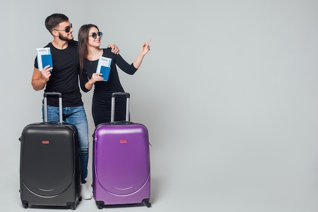 Smiling young happy couple with suitcases and ticket around isolated on white
