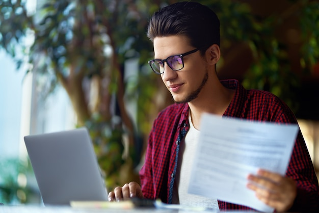 Smiling young hipster man in glasses with laptop on the table. programmer, web developer, designer working at office comparing mobile and desktop website versions.