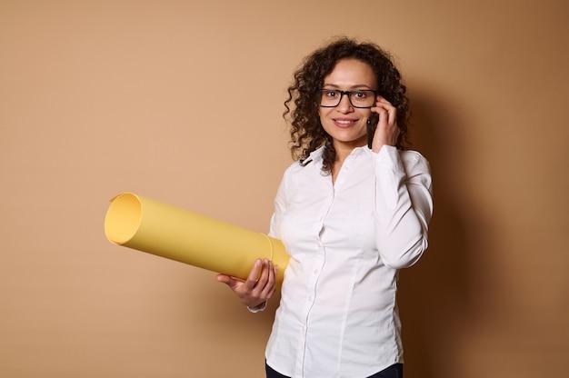 コピースペースでベージュの壁にポーズをとって、黄色のデザイン色紙を持って携帯電話で話している若いヒスパニック系女性の笑顔