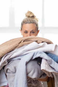 Smiling young housewife holding heap of clothing