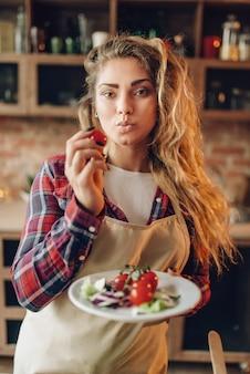 エプロンで笑顔の若い主婦がサラダを準備します。