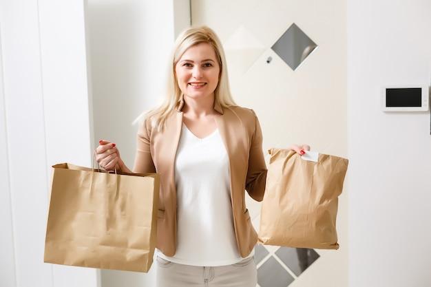 Улыбающаяся молодая домохозяйка с сумкой для покупок, полными продуктами в пакетах