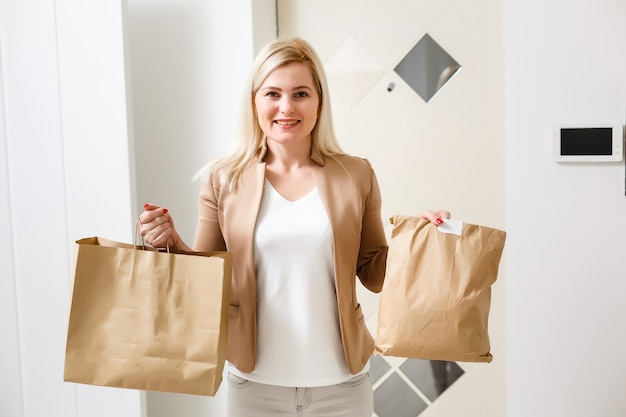 Smiling young housewife with shopping bag, full groceries in packages
