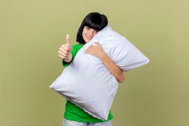 Улыбающаяся молодая больная кавказская девушка обнимает подушку, глядя в камеру, показывая большой палец вверх, изолированный на оливково-зеленом фоне с копией пространства