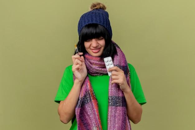 Sorridente giovane ragazza caucasica malata indossando cappello invernale e sciarpa tenendo la siringa e il pacchetto di compresse mediche con gli occhi chiusi isolati su sfondo verde oliva con spazio di copia