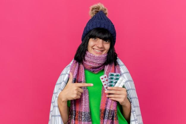 Sorridente giovane ragazza caucasica malata indossando cappello invernale e sciarpa avvolto in plaid holding e indicando pillole mediche che guarda l'obbiettivo isolato su sfondo cremisi con lo spazio della copia