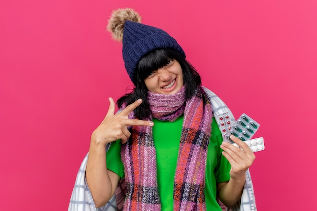 Smiling young ill caucasian woman wearing winter hat and scarf wrapped in plaid holding packs of medical pills, showing three fingers gesture isolated