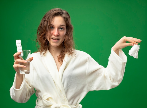 水のwitjピルのガラスを保持し、緑で隔離された側でナプキンを差し出して白いローブを着て笑顔の若い病気の女の子