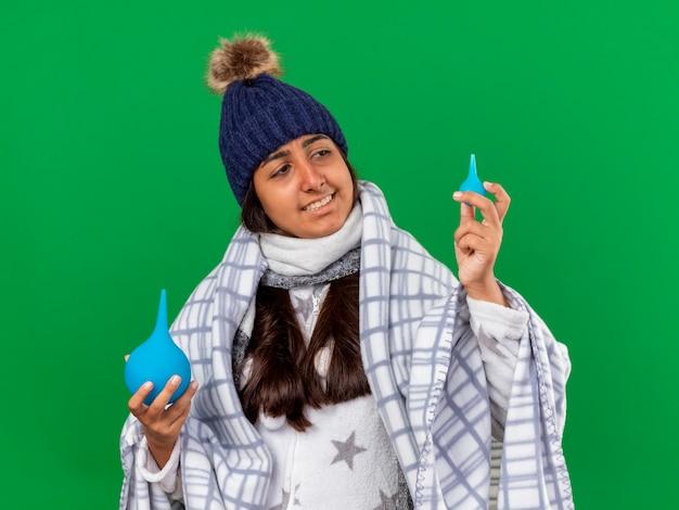 스카프를 들고와 녹색 배경에 고립 된 관장을보고 겨울 모자를 쓰고 웃는 어린 아픈 소녀