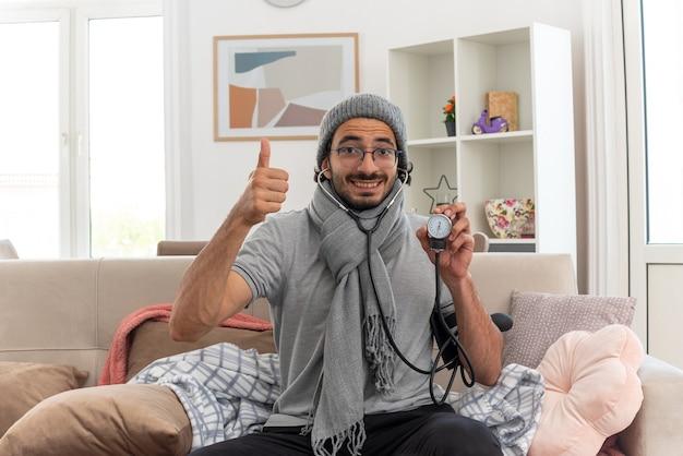 Sorridente giovane malato in occhiali ottici con sciarpa intorno al collo indossando cappello invernale misurando la pressione con sfigmomanometro e pollice alzato seduto sul divano in soggiorno