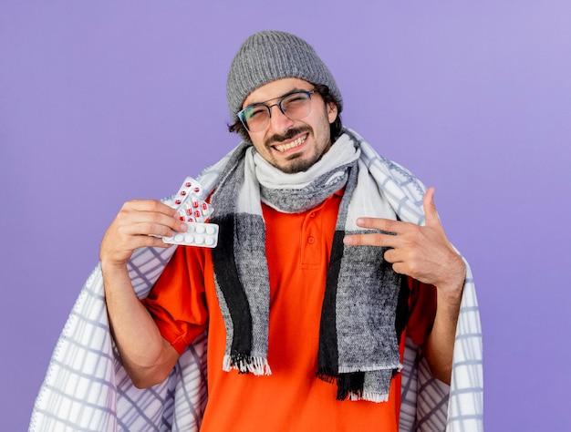 紫の壁に隔離された正面を見て、格子縞の保持と医療薬のパックを指して、眼鏡の冬の帽子とスカーフを身に着けている若い病気の人の笑顔