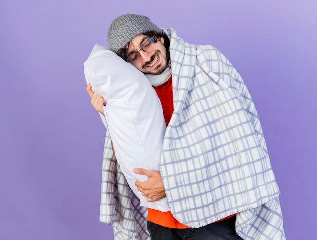 보라색 벽에 고립 된 닫힌 눈으로 그것에 머리를 넣어 베개를 들고 격자 무늬에 싸여 안경 겨울 모자와 스카프를 착용하는 젊은 아픈 남자를 웃고