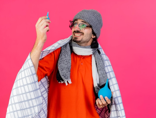 Smiling young ill man wearing glasses winter hat and scarf wrapped in plaid holding enemas looking at little one isolated on pink wall with copy space