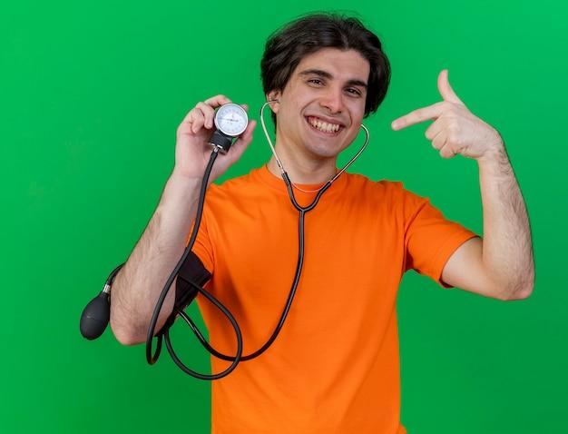 Sorridente giovane uomo malato che indossa stetoscopio holding e punti a sfigmomanometro isolato su verde