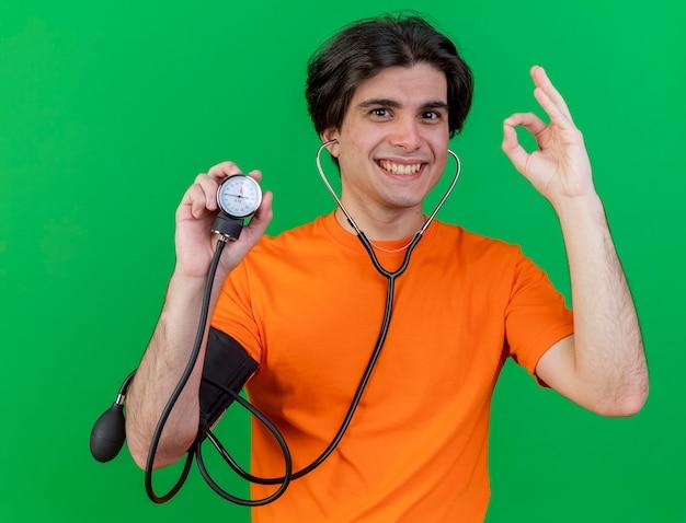 Улыбающийся молодой больной человек со стетоскопом, держащий сфигмоманометр, показывающий жест окей, изолированный на зеленом фоне