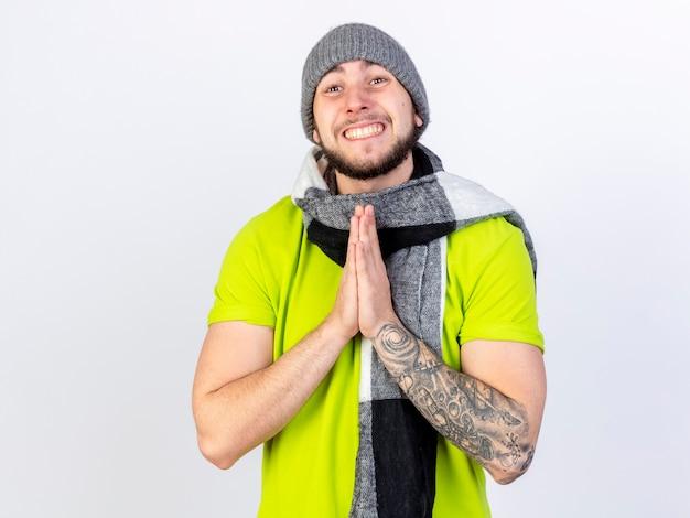 Улыбающийся молодой больной человек в зимней шапке и шарфе держит руки вместе, изолированные на белой стене