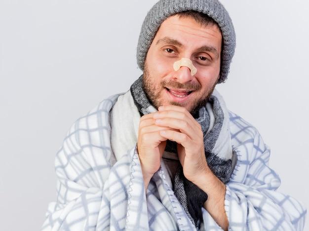 Sorridente giovane uomo malato che indossa cappello invernale e sciarpa avvolti in un plaid con intonaco sul naso che tengono le mani sul mento isolato su bianco