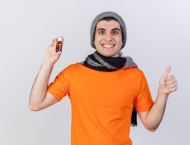 엄지 손가락을 보여주는 유리 병에 약을 들고 스카프로 겨울 모자를 쓰고 웃는 젊은 아픈 남자