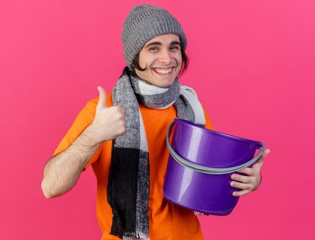 분홍색 배경에 고립 엄지 손가락을 보여주는 플라스틱 양동이 들고 스카프와 겨울 모자를 쓰고 웃는 젊은 아픈 남자