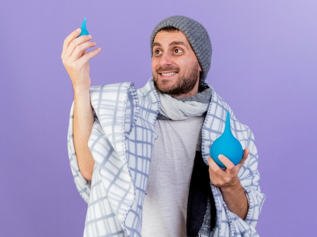 Sorridente giovane uomo malato che indossa cappello invernale con sciarpa che alza e guardando clistere isolato su sfondo viola