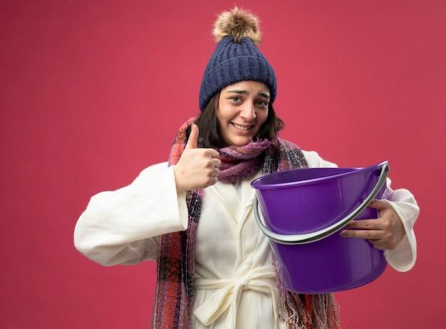 가운 겨울 모자와 스카프를 입고 웃는 젊은 아픈 여자는 분홍색 벽에 고립 된 전면을보고 엄지 손가락을 보여주는 플라스틱 양동이를 들고
