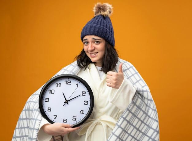 Sorridente giovane donna malata che indossa un abito invernale cappello avvolto in plaid tenendo l'orologio guardando la parte anteriore che mostra il pollice in alto isolato sulla parete arancione