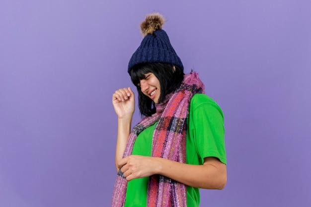 Улыбающаяся молодая больная женщина в зимней шапке и шарфе, стоящая в профиль, держа руку в воздухе с закрытыми глазами, изолированными на фиолетовой стене
