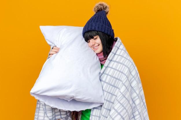 오렌지 벽에 고립 된 닫힌 눈 베개로 머리를 만지고 베개를 들고 격자 무늬에 싸여 겨울 모자와 스카프를 입고 웃는 젊은 아픈 여자