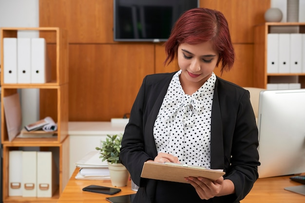 Smiling young indian businesswoman taking notes in documents on clipboard when stading at desk in her office
