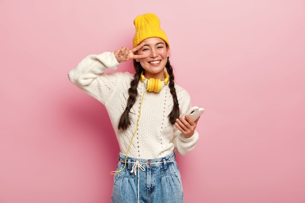 Smiling young korean woman makes peace gesture over eye, holds modern cell phone, has two plaits, smiles gently, wears yellow hat and jeans, poses against pink background.