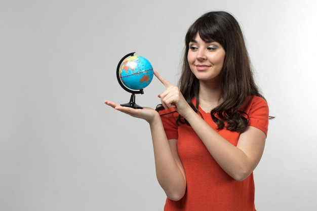Smiling young lady in designed t-shirt in good mood with long hair holding globe on white