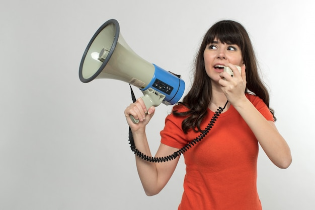 Smiling young lady in designed t-shirt using megaphone in good mood with long hair on white