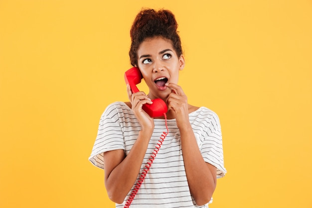 Smiling young lady holding red handset isolated