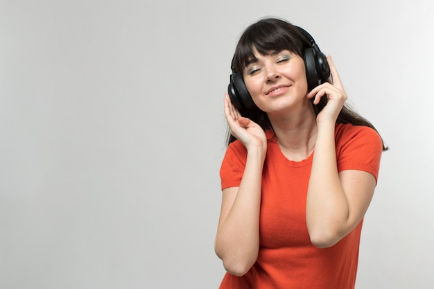 Smiling young lady listening to music through earphones in designed t-shirt in good mood with long hair on white