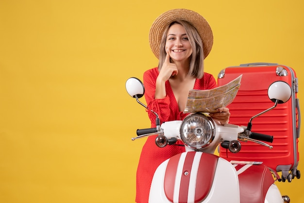 Smiling young lady in red dress holding map near moped