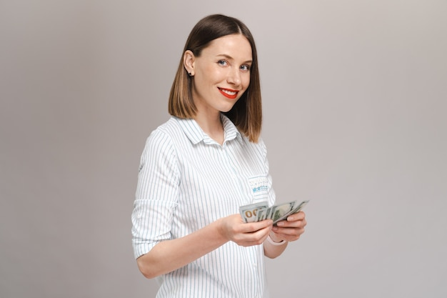 Smiling young lady in striped shirt holding money and looking to them over gray wall looking to front