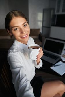 Улыбающаяся молодая леди, использующая смартфон для селфи во время перерыва на кофе дома