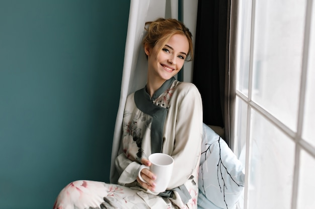 Smiling young lady with cup of coffee, tea in her had, sitting on window sill, good morning relax. wearing silk pajamas in flowers, has blonde hair. photo in turquoise colors.