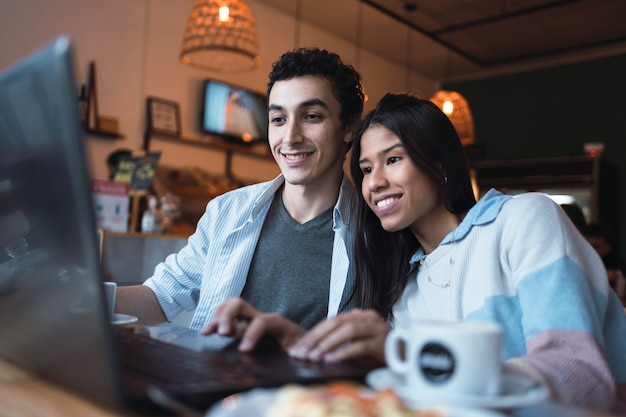 A smiling young latino couple looking at a laptop in a bar.
