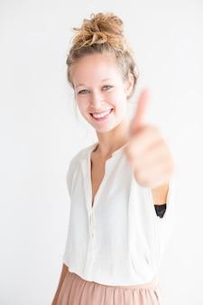 Улыбаясь молодая симпатичная женщина показывает большой палец вверх