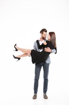 Улыбающиеся молодые влюбленные стоя изолированы