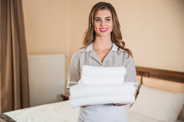 Smiling young maid holding white stack of towels standing in front of bed