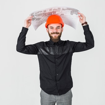 Smiling young male architect holding blueprint over his head