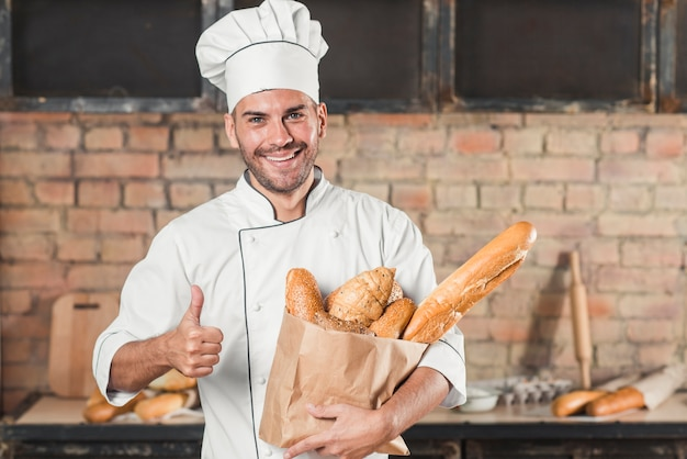 Smiling young male baker holding loaf of breads in paper bag showing thumb up sign
