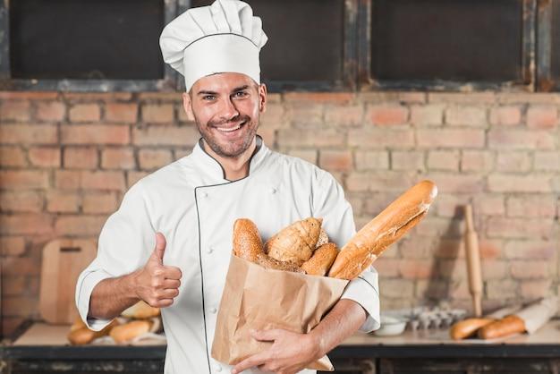 Улыбаясь молодой пекарь, проведение буханки хлеба в бумажный мешок, показывая пальцем вверх знак
