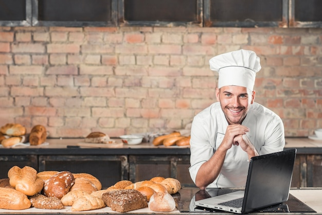 Smiling young male baker leaning on table with variety of baked bread and laptop